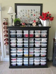 Although I'm not a big fan of a storage system dominated by plastic, this one works because it is so neatly contained. The shelf border, lamp, flowers and pin board make this a happy solution.