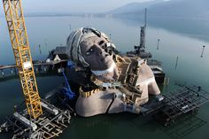 A 15-meter (49-foot) head was fixed on a torso with cranes and integrated into a floating stage on Lake Constance near Bregenz, Austria, Thursday. It is part of the stage setting for the opera 'Andre Chenier' by Italian composer Umberto Giordano, which will premiere in July. (Felix Kaestle/Associated Press)