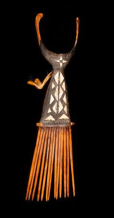 Solomon Island | Flat comb made with strips of coconut wood lashed together middle area covered in a black gum with inlaid shell and leading to a delicate crescent shaped finials at top
