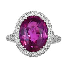 6.47 Carat Oval Pink Sapphire & Diamond Ring. Platinum cluster ring consisting of 1 oval shaped pink sapphire weighing 6.47 carats set with .85 carats total weight of round brilliant cut diamonds surrounding the center stone and going down the shoulders and a filigree under gallery. 21st century.