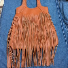 JustFab fringe bag NWT I love this bag I just never going to use it. Maybe if I didn't always leave the house with a diaper bag and I actually had a life. Haha it is just a crime to leave this bag sitting and not use it. If it doesn't sell them maybe one day I will take her for a stroll. But she deserves to be loved every day. Awesome fringe detail I love the depths of the inside of this bag! Great pockets inside too! Even on the backside of the outside! ❤️ cognac brown color JustFab Bags…