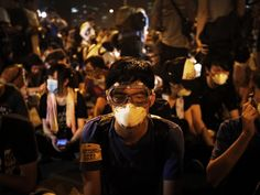 Student protesters donning masks and goggles to ward off pepper spray and tear gas have become powerful images of the 'umbrella revolution.' Here, they sit on the main road outside the government complex where Hong Kong chief executive Leung Chun-ying has an office.