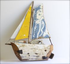 Hand made boat from wood scraps washed up on the beach. Hull is part of an old mast. At coastal vintage.
