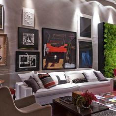 No ambiente criado por Paola Ribeiro na mostra de decoração CasaCor SP 2013, a sala de estar ganhou uma imponente parede forrada de pôsters e quadros. A ideia é bacana para uma decoração da sala de estar mais masculina e sóbria.
