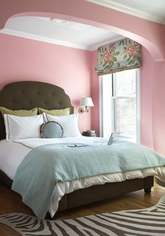 pink blue green bdroom design with pink walls paint color, olive green tufted bed headboard, green shams, white hotel bedding with black stitching, blue throw, swing-arm sconces, zebra rug and pink blue green floral roman shade