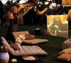 For a low-key get together, do a DIY drive-in movie in your backyard with a projector, twinkle lights, cushions and popcorn