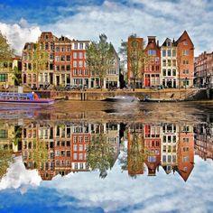 Leoks nous présente la ville d'Amsterdam avec ses charmantes bâtisses colorées qui se reflètent magnifiquement sur un de ses canaux.