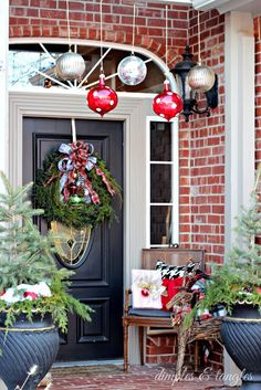 Christmas front porch ideas, evergreens in urns, hanging oversized ornaments, vintage chair, sled, and ice skates