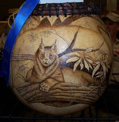 "Lynx Bowl by Karen Hundt-Brown. This Michigan grown gourd bowl features an amazing rendering of a Lynx in lounging on a tree branch. This piece is all wood burned (pyrography) and has the illusion of looking through the leaves at a beautiful Lynx. Size  9""H x 8""W. $375. On Artful Vision, www.artfulvision.com a portion of your purchase is donated to a participating non-profit of your choice. #art #bowl #home_decor #gift #Lynx #wood"