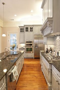 #Kitchen of the Day: A luxury kitchen with gray cabinets, dark granite, a glass mosaic backsplash, oak floors, and a decorative wood hood.