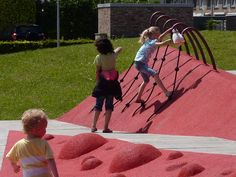Van Campenvaart playground, Den Hague, Netherlands.  This new playground is located on an existing lawn and shaped as a folded red blanket with a strong graphic character. The undefined possibilities of the field challenges the boundaries of both (partially)disabled and non-disabled children. Intersecting routes allow children with different abilities to meet and help each other.