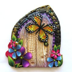 A little door with a Monarch Butterfly friend. A few crystals added for some sparkle. (Fairies like that!) Each fairy portal is handcrafted by me so each one is unique and most are OOAK. Doors measure approximately 3.5 to 4.0  in size.  Hand crafted from polymer clay and fairy dust. You will receive the exact door in the first three pictures.  Just stick the magical Fairy Door to a wall in your house and all of your neighborhood fairies will have a much easier time gaining access to your…