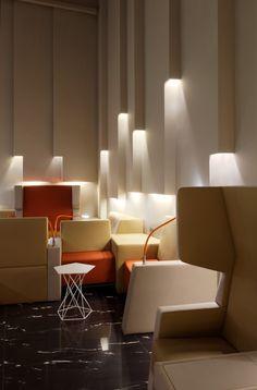 Parecem tipos de tubos acoplados na parede trazendo luz dentro deles, achei super interessante. Como os móveis do ambiente ja possuem cores mais quentes, foi usada uma iluminação mais neutra, oq trouxe um contraste ao ambiente.