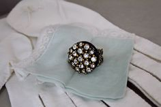 Handcrafted ring with vintage rhinestone buttons and a vintage black button from Emma Lou Vintage
