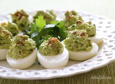 """My mom adds hard boiled eggs to her guacamole, so I thought why not add guacamole to hard boiled eggs? The results were lovely, and since I was testing them out for the blog, I actually enjoyed them for lunch. These are a fun, """"clean"""" snack or appetizer, not just as a green food for St Patrick's day, but for anytime of the year. Loaded with a good dose of healthy fats and perfect for any dietary restriction – vegetarian, gluten-free, weight watchers, low-carb, paleo, and more! Guacamo..."""