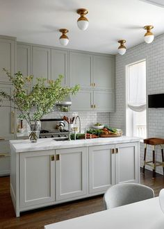 BECKI OWENS - Pinterest Top 10 - Visit the blog to see the top trending images on my boards this month! Like this pretty green gray kitchen with Prada flushmount lighting.