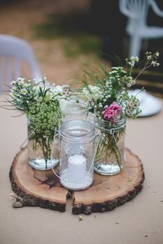 How pretty is this rustic chic centerpiece? It features wooden tree slices and mason jars filled with blue thistle, daisies and wild flowers. {Jessica Cruz Photography}
