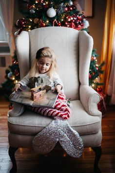 Nestled in her holiday mermaid tail by @thetropicalmermaid, reading her pop-up book!