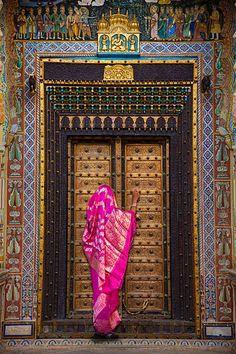Vibrant fuchsia sari and golden Indian door.