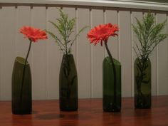 wine bottle vases cut at an angle. Could be easy DIY with just glass cutter!!