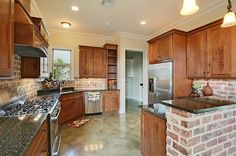 Huge catering kitchen, complete with stainless gas range, and brick accents everywhere.