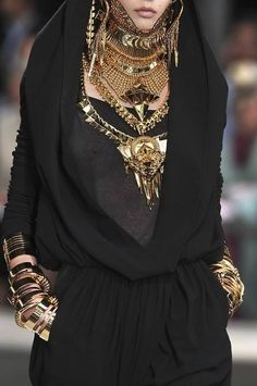 Givenchy Black and gold , shiny texture with curved lines  Emphasis in the jewelry and necklaces