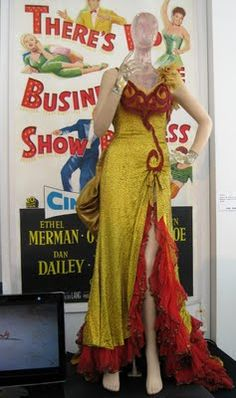 Saloon girl dress worn by Marilyn Monroe in River Of No Return. Gold charmeuse gown covered with bugle beading, red fringe accents, and gold velvet train with red netting.