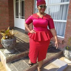 Lady In Mixed To Match Red and Pink Shweshwe Peplum Cold Shoulder Dress and Headwrap Couples African Outfits, African Dresses For Women, African Attire, African Wear, African Clothes, Seshweshwe Dresses, Office Wear Dresses, Seshoeshoe Designs, South African Traditional Dresses