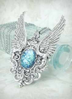 Treasure of Atlantis - Steampunk Angel Wing Necklace by RavynEdge. https://www.etsy.com/listing/125235839/treasure-of-atlantis-steampunk-necklace Magnificent angel wings and flourishes of filigree encase a gorgeous aquamarine harlequin art glass opal. This piece was made to impress. Looks equally amazing on a man or a woman. Wear it with a costume or for an everyday fashion statement!