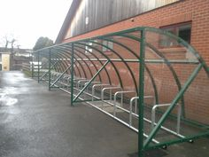 The Park Community School, Barnstaple - Four bays of FalcoQuarter cycle shelter with four 5 place Toast racks to accommodate 40 bikes. Steelwork powder coated in RAL 6005 Moss Green.