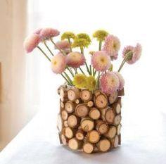 DIY Florero con rodajas de ramas, en un envase de plástico o similar.