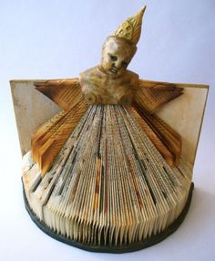 Words, porcelain doll bust , altered book, found and made objects, bee's wax