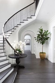 Chic, classic foyer features a curved staircase wall filled with a black round table and orchids.