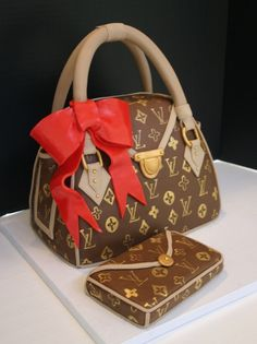 Handpainted Louis Vuitton purse cake created using chocolate fondant with a red fondant bow