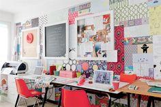 Líneas netas y detalles de color en un espacio de trabajo  Contra una de las paredes, revestida con un collage de los diseños de la marca, apoyaron sendos tableros de dibujo reciclados como escritorios de trabajo.