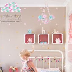 Miniature polka dot decals on a wall behind a bed headboard in a girl's bedroom.