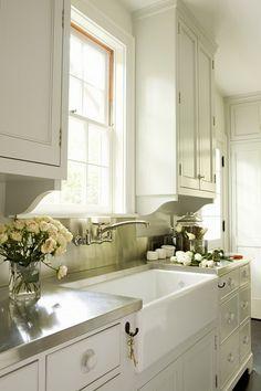 white kitchen w/ stainless steel countertops + farmhouse sink