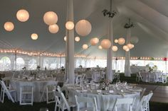 White paper lanterns in a large tent with decorated poles in Farmington, CT.