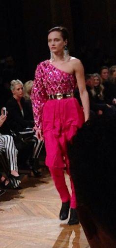 Karmen Pedaru avec top asymétrique et un pantalon rose vif au défilé @Balmain #PiagetRose