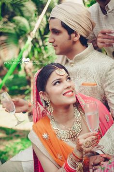 Real Indian Weddings - Nupur and Adhish | WedMeGood | Candid Couple Shot with the Groom Wearing a Gold Sherwani and Turban and the Bride in an Orange and Candy Pink Lehenga with a Polki Necklace and Gold Maang Tikka Picture Courtesy: Chasing Dreams #wedmegood #realwedding #candid #couple #orange #gold #polki
