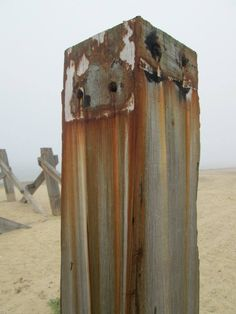 Rusty rainbow groyne post.