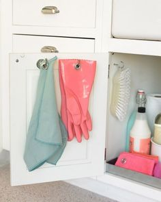 Hang kitchen rags and dishwashing gloves from hooks screwed to the inside of a cabinet door, where they can stay out of sight as they dry.