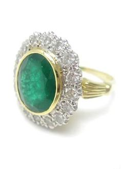 An 18ct gold emerald and diamond cluster ring  Set with an oval-cut emerald to a rubover setting surrounded by a row of round brilliant-cut diamonds to claw settings, between reeded, tapered shoulders, to a plain hoop, size O, the emerald estimated to weigh approximately 3.80cts, the diamonds estimated to weigh approximately 0.56ct in total
