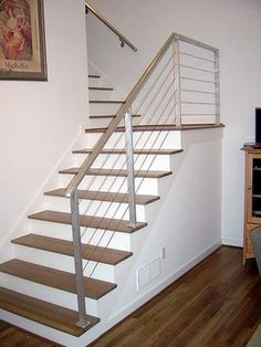 Stairs after remodeling with dark hardwood floor, wire and brushed metal railing and painted walls