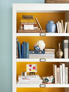 A simple bookshelf makes big impact, thanks to color and tag holders. If you are reluctant to paint, a quick & easy fix: cover cut-to-size lightweight board with fabric. Easy switch-out.