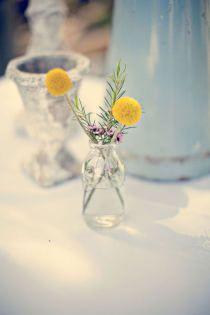Du romarin et de simples fleurs dans de petits vases transparents