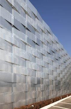 Ribbons of wave-like perforated steel form a mask, the second façade of this old warehouse. Colour variations highlighted by light changes produce unexpected chequered patterns as well as silver and gold toning enhancing the façade's versatile nature.