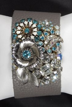 My newest bracelet creation! An assemblage of antique costume jewelry in shades of blues and white rhinestones on a super soft leather cuff bracelet.