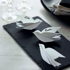 Marque-place en papier en forme d'oiseau avec nom de l'invité inscrit sur une aile