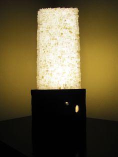 Luminária (19,5x22x54 cm) Superfície musiva realizada em técnica direta, utilizando material natural (pedra ônix) cortada manualmente e desgastada para reproduzir o efeito de pedra rolada. Estrutura em madeira (peroba) e acrílico com iluminação LED.